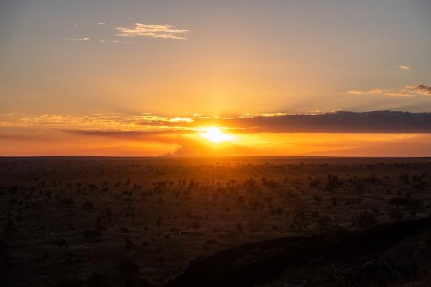 Zapierający dech w piersiach zmierzch w kolorowym niebie nad pustynią w tsavo zachodzie, kenja, kilimanjaro