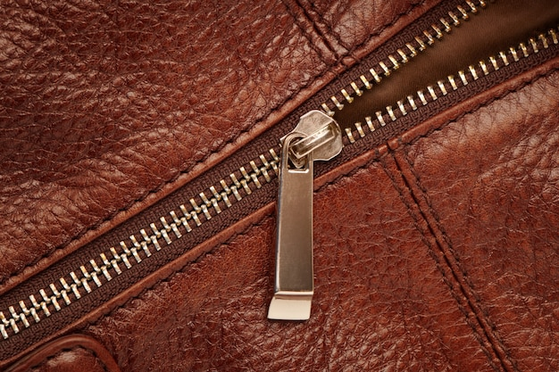 Zapinana na metalowy zamek błyskawiczny na brązowej skórzanej torbie