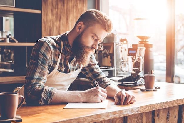 Zapisywanie nowych przepisów na kawę. młody brodaty mężczyzna w fartuchu, piszący w notatniku, pochylając się do baru w kawiarni