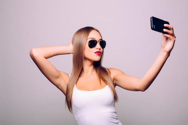 Zapisywanie pamięci o jej nowym stylu. portret pięknej młodej kobiety w okularach, dostosowując jej kapelusz podczas robienia selfie i stojąc przed szarej ścianie