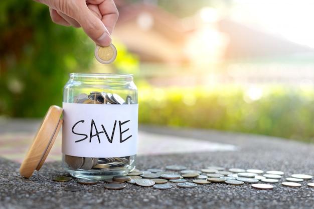 Zapisz koncepcja pieniędzy z ręki trzymającej monety i monety w butelce na tle bokeh