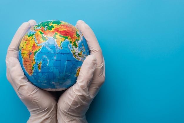 Zapisz koncepcję planety. osoba w rękawiczkach trzyma małą planetę ziemię odizolowaną na niebieskim tle