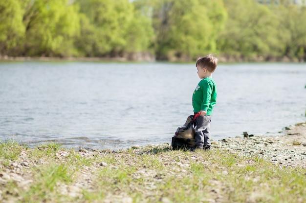 Zapisz koncepcję środowiska, małego chłopca zbierającego śmieci i plastikowe butelki na plaży
