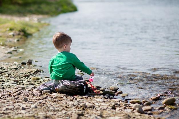 Zapisz koncepcję środowiska, mały chłopiec zbierający śmieci i plastikowe butelki na plaży, aby wyrzucić je do kosza.