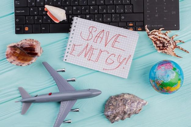 Zapisz słowa energii w notatniku w kompozycji podróżnej. samolot, kula ziemska, muszle na niebieskim biurku.