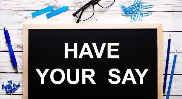 Zapisz swoje mówienie napisane na czarnej tablicy obok niebieskich spinaczy, ołówków i długopisu