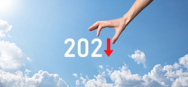 Zaplanuj negatywny wzrost biznesu w koncepcji roku 2021. biznesmen plan i wzrost negatywnych wskaźników w jego biznesie, spadek koncepcji biznesowych. trzymaj rękę na tle nieba