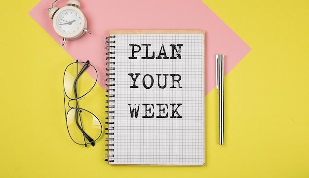 Zaplanuj tydzień ogłoszenie na zeszycie z długopisem, okularami i budzikiem