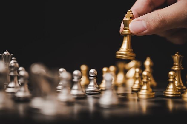 Zaplanuj wiodącą strategię udanej koncepcji lidera konkurencji biznesowej, ręka gracza szachowej gry planszowej stawiając złoty pionek