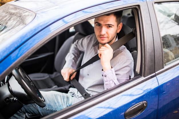 Zapnij pas samochodowy. młody człowiek najpierw bezpieczeństwo pasa bezpieczeństwa podczas jazdy