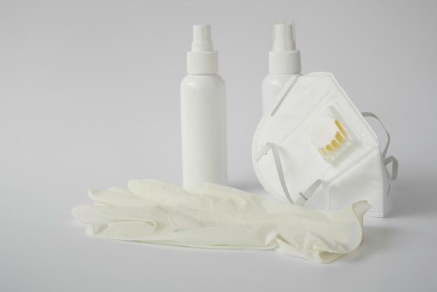 Zapobieganie koronawirusowi za pomocą medycznej maski chirurgicznej i rękawiczek, dezynfekującego alkoholu w sprayu do rąk