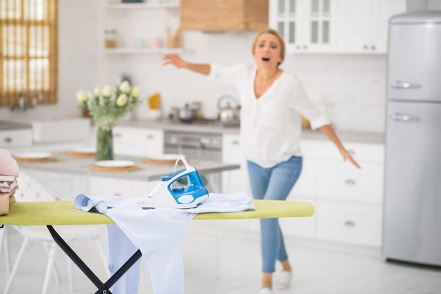 Zapomniane robocze żelazko leżące na koszuli i zmartwiona kobieta z tyłu kuchni
