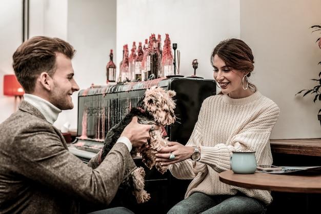 Zapoznanie się z nowym członkiem rodziny. mężczyzna podający psa dla swojego partnera