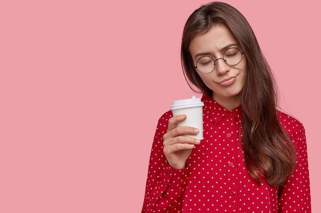 Zapracowana ciemnowłosa kobieta wygląda sennie, niesie w rękach kawę na wynos, drzemie podczas przerwy, ubrana w stylowy strój