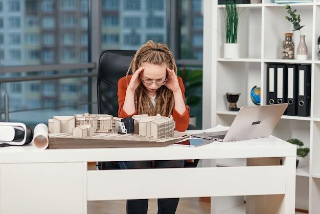 Zapracowana kobieta biznesu odczuwa stres związany z problemami z projektem architektonicznym i projektowym przyszłego budynku.