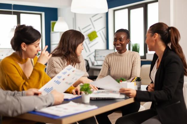 Zapracowane wielokulturowe pracownice analizujące roczne statystyki finansowe, siedzące przy biurku, trzymające dokumenty szukające rozwiązań biznesowych