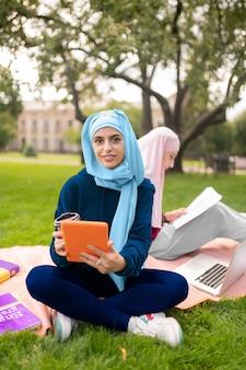 Zapracowani muzułmańscy studenci. widok z góry na muzułmańskich uczniów korzystających z gadżetu podczas nauki języka obcego
