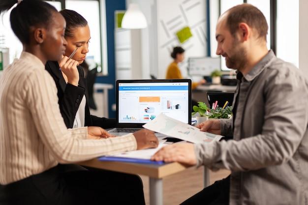 Zapracowani, wielokulturowi, różnorodni pracownicy analizujący roczne statystyki finansowe siedzący przy biurku przed laptopem trzymający dokumenty w poszukiwaniu rozwiązań biznesowych