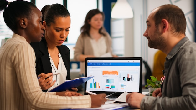 Zapracowani, wielokulturowi, różnorodni pracownicy analizujący roczne statystyki finansowe, siedzący przy biurku przed laptopem trzymającym dokumenty w poszukiwaniu rozwiązań biznesowych. zespół przedsiębiorców pracujących w firmie