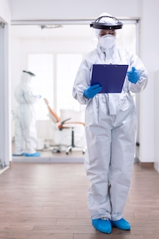 Zapracowany lekarz w garniturze przeciwko skażeniu koronawirusem piszący notatki w schowku. personel medyczny ubrany w sprzęt ochronny przed zakażeniem covid-19 podczas globalnej pandemii.