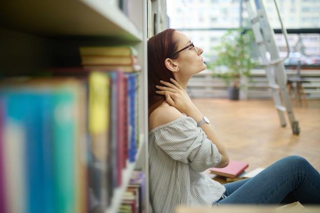 Zapracowany naukowiec siedzący na podłodze w bibliotece