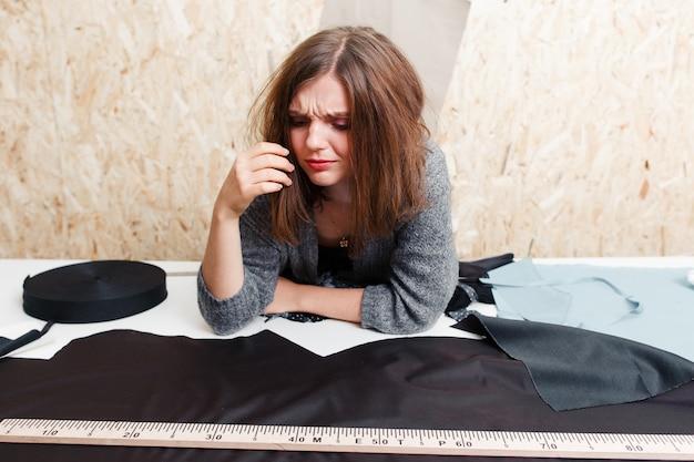 Zapracowany projektant płaczący nad materiałem.