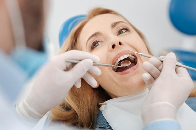 Zapracowany, wykwalifikowany lekarz, który używa specjalnych narzędzi do sprawdzania i czyszczenia zębów, podczas gdy kobieta trzyma otwarte usta