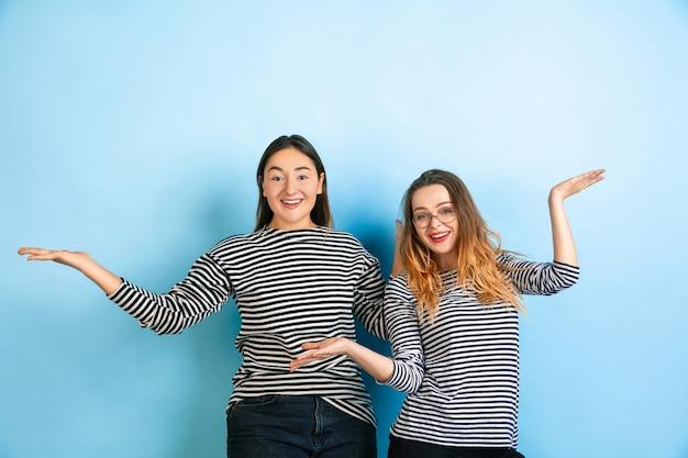 Zapraszanie, pozdrowienie. młode emocjonalne kobiety na białym tle na gradientowej niebieskiej ścianie. pojęcie ludzkich emocji, wyraz twarzy, przyjaźń, reklama. piękne modele kaukaskich w codziennych ubraniach.