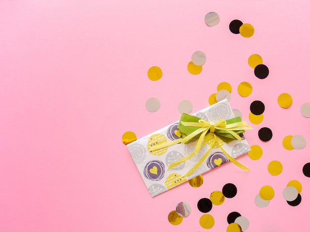 Zaprojektuj kopertę z zieloną wstążką na różowo. kartka urodzinowa z kolorowymi konfetti.