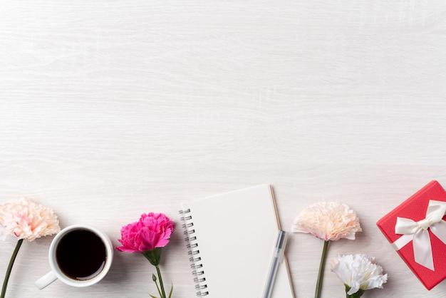 Zaprojektuj podsumowanie dnia matki z kwiatem goździka, pomysłem na prezent świąteczny i pamiętnik notatnika na tle biurka matki.