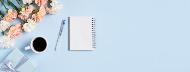 Zaprojektuj podsumowanie życzenia dnia matki z kwiatem goździka, pomysłem na prezent świąteczny i pamiętnik notatnika na tle biurka matki.