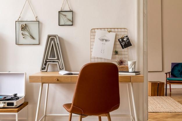 Zaprojektuj skandynawskie wnętrze domowego biura z dużą ilością ramek na zdjęcia, drewnianym biurkiem, brązowym krzesłem, fabryką gramofonów, akcesoriami biurowymi i osobistymi. stylowa neutralna home inscenizacja