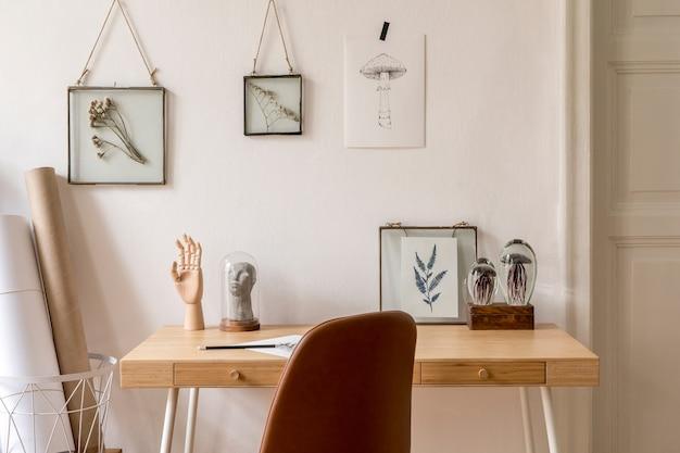 Zaprojektuj skandynawskie wnętrze domowego biura z dużą ilością ramek na zdjęcia, drewnianym biurkiem, brązowym krzesłem, roślinami, akcesoriami biurowymi i osobistymi. stylowa neutralna home inscenizacja..