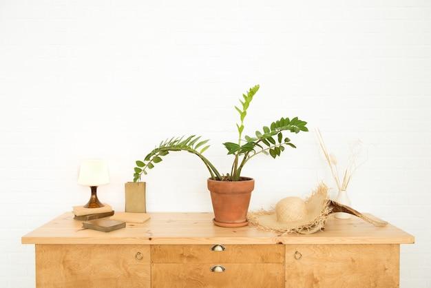 Zaprojektuj wewnętrzny drewniany stół z książkami i rośliną