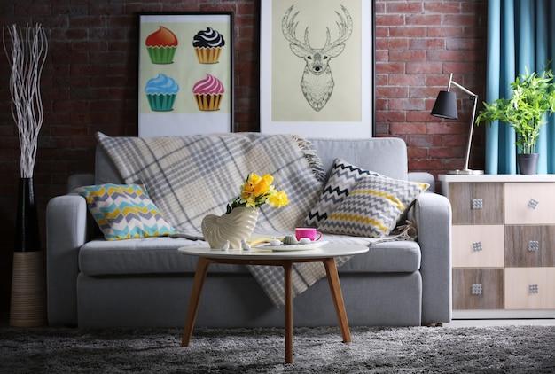 Zaprojektuj wnętrze salonu z szarą sofą i bukietem kwiatów na stole