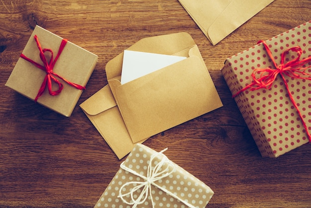 Zaproszenia na imprezę. zbliżenie z góry na pudełka na prezenty i otwarte koperty leżące na rustykalnym drewnianym słoju