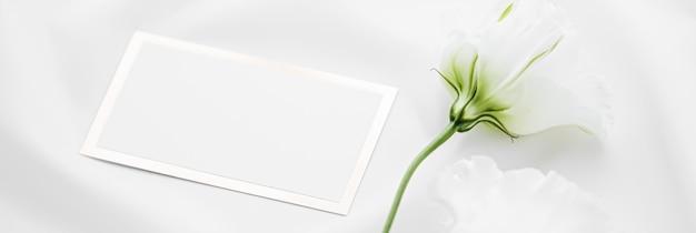 Zaproszenie na ślub lub karta podarunkowa i białe kwiaty róży na jedwabnej tkaninie jako wesele flatlay tło b...