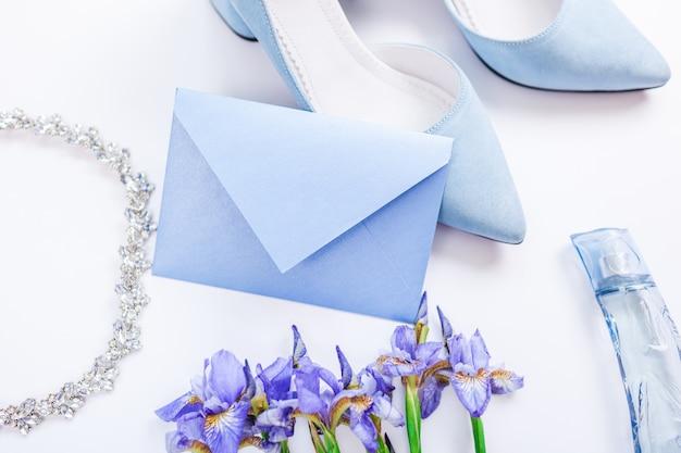 Zaproszenie na ślub otoczone kwiatami, butami panny młodej, perfumami i biżuterią