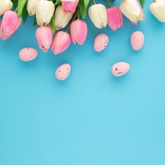 Zaproszenie wielkanocne z tulipanami na niebieskim tle z miejsca na kopię