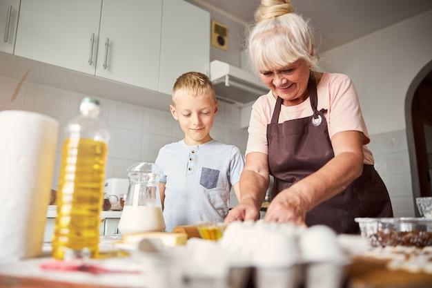 Zaprzyjaźniona starsza kobieta gotuje razem z wnukiem