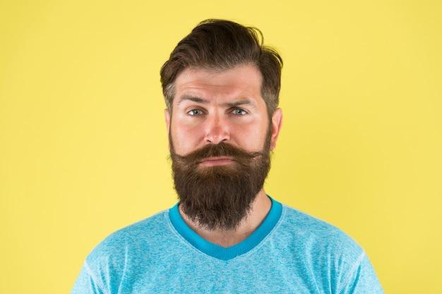 Zapuść wąsy. zapuszczanie i pielęgnacja wąsów. hipster brodaty mężczyzna z wąsem. przewodnik po pielęgnacji brody i wąsów. hipster przystojny brodaty facet atrakcyjny żółtym tle. koncepcja sklepu fryzjerskiego.