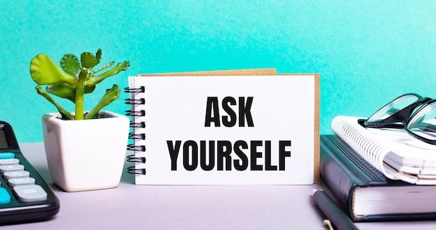 Zapytaj siebie jest zapisane na białej karcie obok kwiatka w doniczce, pamiętników i kalkulatora