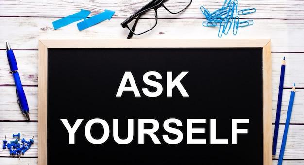 Zapytaj siebie napisane na czarnej tablicy obok niebieskich spinaczy, ołówków i długopisu