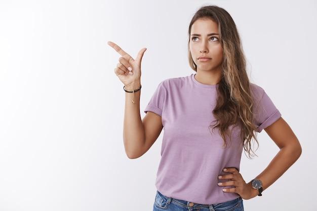 Zapytana wątpliwa, przystojna jasnowłosa kaukaska kobieta marszczy brwi, dąsając się, widząc dziwną rzecz wskazującą, wyglądającą na rozczarowaną, niepewną, marszczącą brwi, niezdecydowaną, stojącą na białej ścianie niepewną