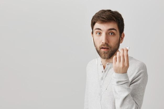 Zapytany facet zdejmuje słuchawkę, żeby usłyszeć