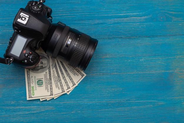 Zarabiaj pieniądze w internecie dslr aparat fotograficzny, dolary, laptop, na niebieskim tle drewnianych, widok z góry