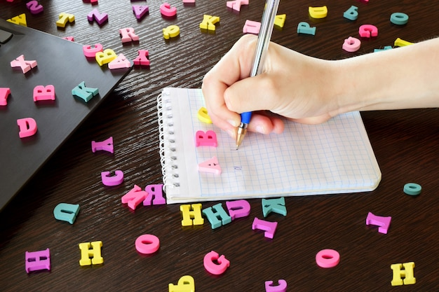 Zarabianie angielskiego to internetowy program do nauki języka angielskiego. mały chłopiec pisze angielskie litery w zeszycie z piórem na domowym ciemnym drewnianym stole z bliska.