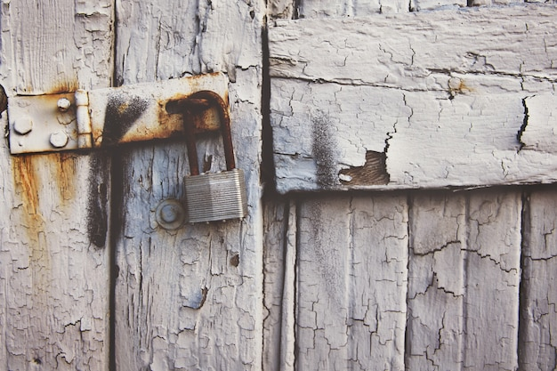 Zardzewiała kłódka wisząca na starożytnej białej drewnianej bramie