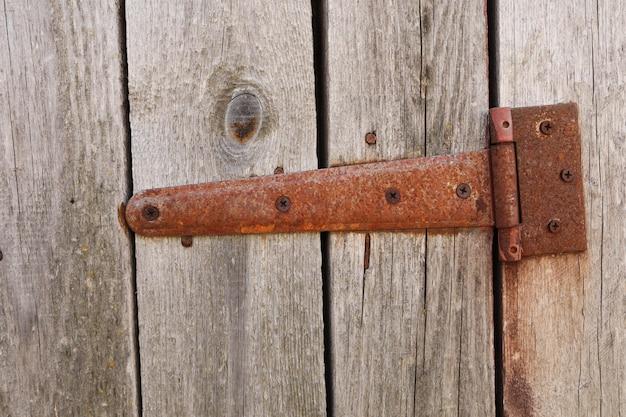 Zardzewiała kuta kurtyna na drewnianych drzwiach.