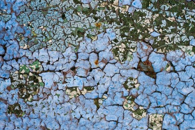 Zardzewiała metalowa powierzchnia z niebieską farbą łuszczącą się i pękająca tekstura tło